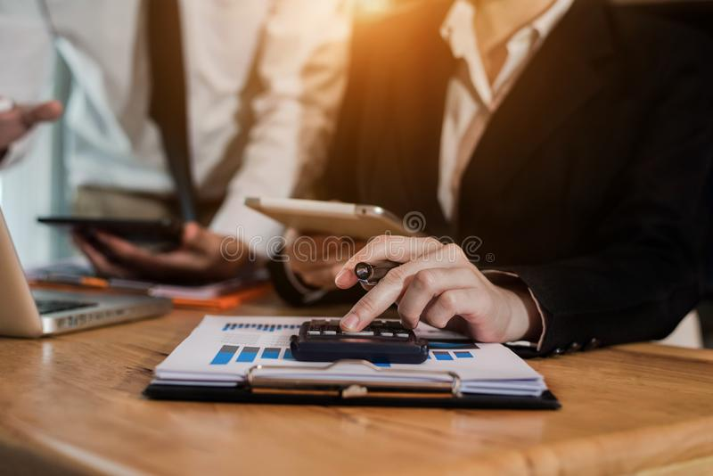 Businessmen or financial data analysts working with tablets and laptop computers and data graphs together. Plan to analyze projects in the office stock images