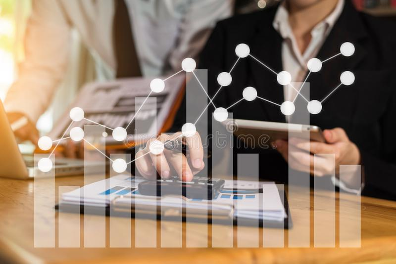 Businessmen or financial data analysts working with tablets and laptop computers and data graphs together. Plan to analyze projects in the office royalty free stock photo