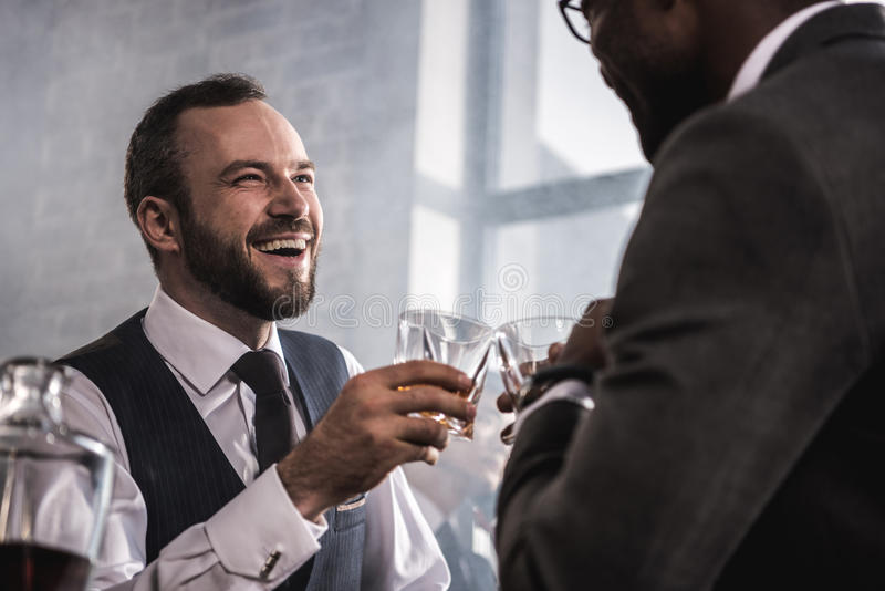 Businessmen in formal wear clinking whiskey glasses and talking stock image