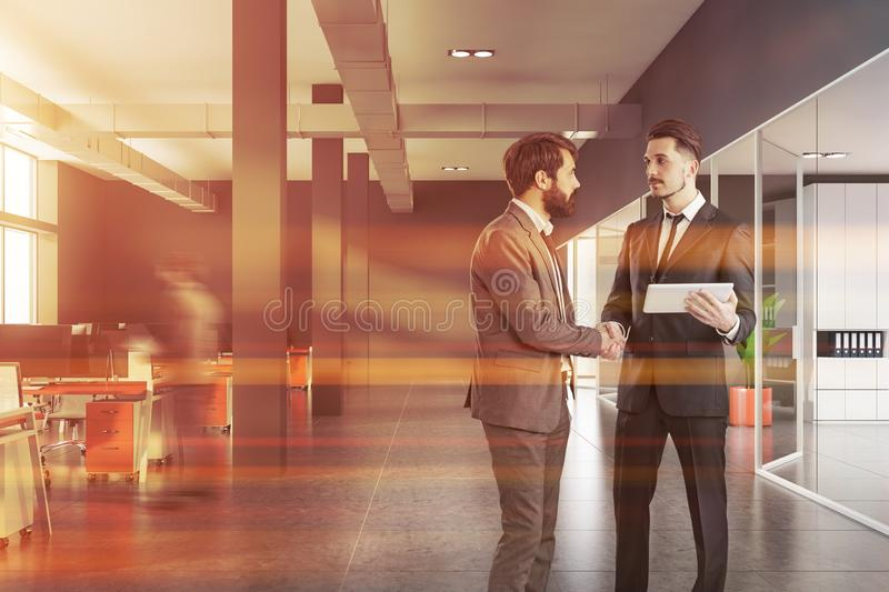 Businessmen in gray office hall royalty free stock images