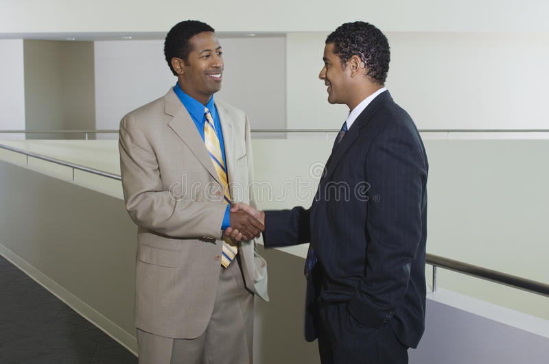 Businessmen Greeting Each Other In Office Hallway. Happy African American businessmen greeting each other in office hallway stock images