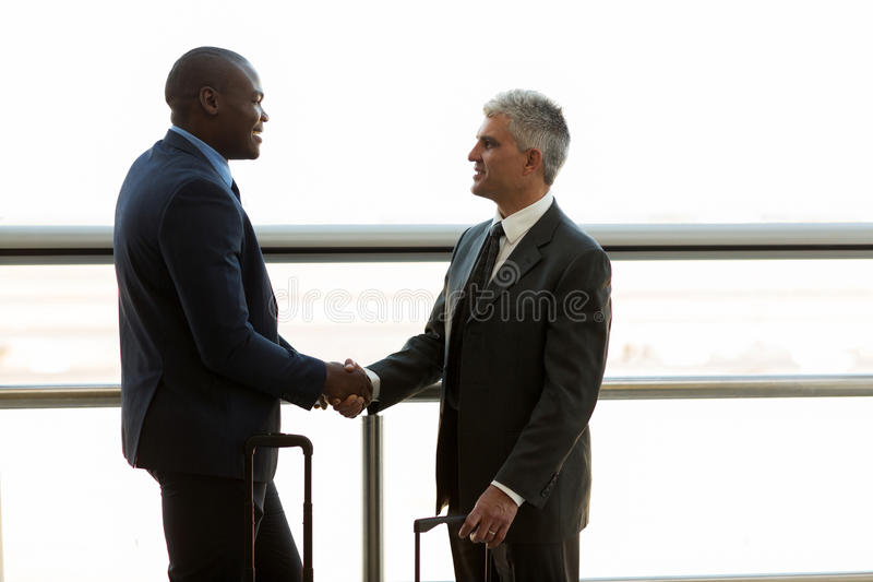 Businessmen hand shaking. Two professional businessmen hand shaking at airport stock photo