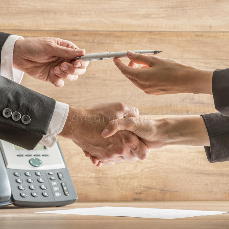 Businessmen Hands Holding Pen While in Handshake. Conceptual Businessmen Hands Holding Pen While in a Handshake Over the Table with Contract, Captured in Close royalty free stock photography