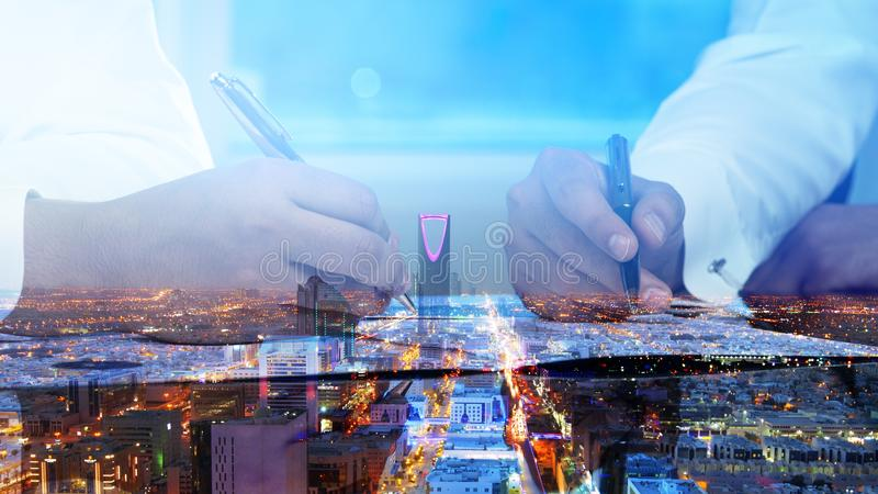 Businessmen hands signing documents on Riyadh skyline city scape background stock photo