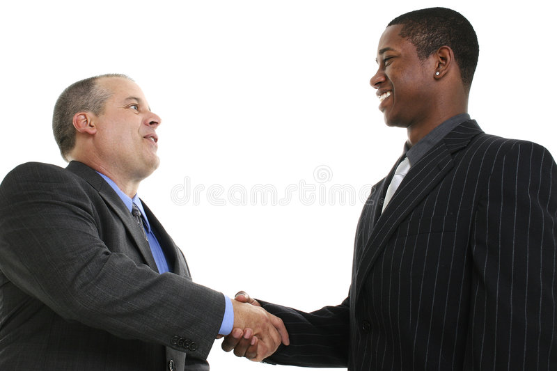 Businessmen Handshake. Two businessmen smiling and shaking hands. Shot in studio over white stock photography