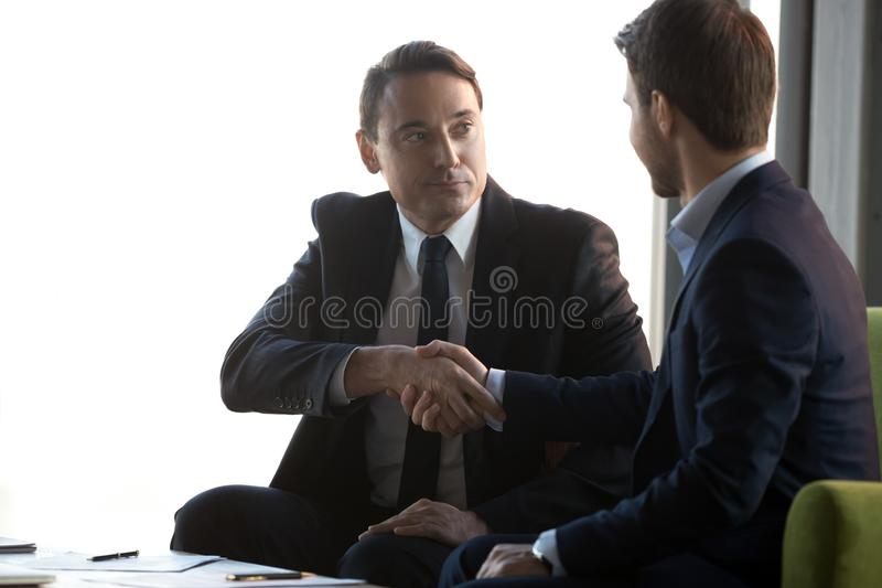 Businessmen handshake signing contract closing successful deal. Serious businessmen shake hands sitting in office after successful negotiations, signing contract royalty free stock photography