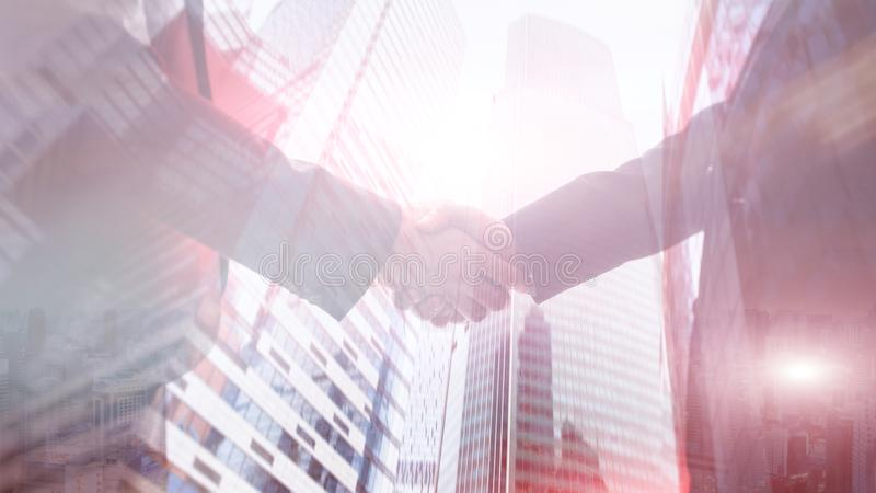 Businessmen handshaking on the background of buildings stock images