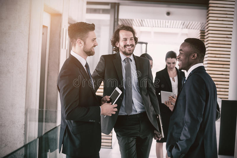 Businessmen having conversation. Happy businessmen having conversation in office stock images
