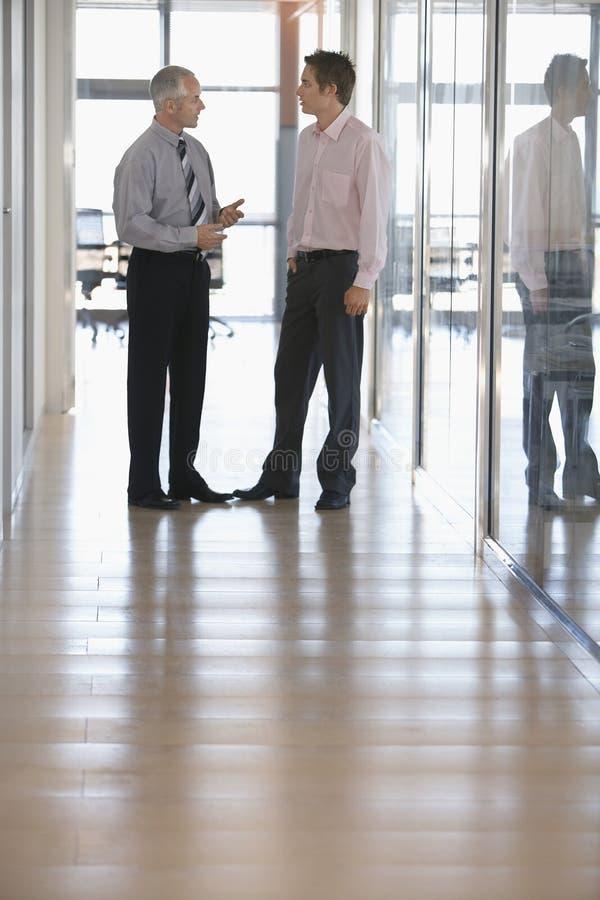 Businessmen Having A Discussion In Corridor stock photos