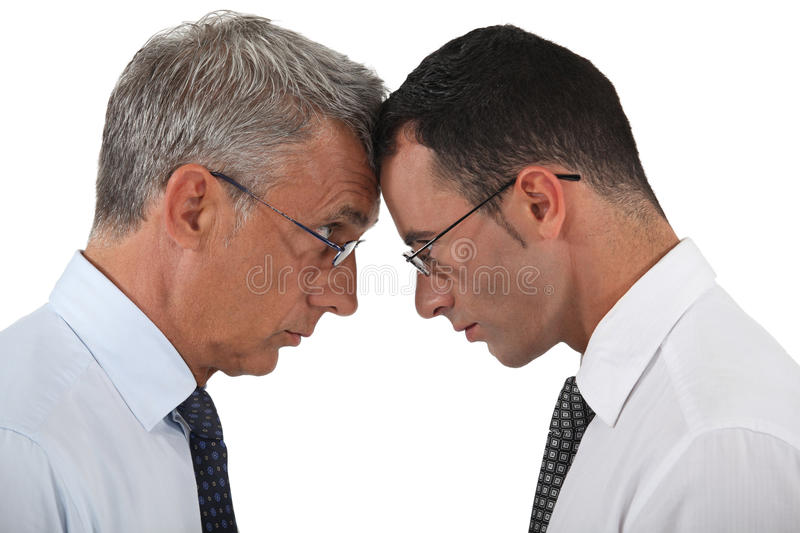 Businessmen head to head. Businessmen stood head to head stock photo