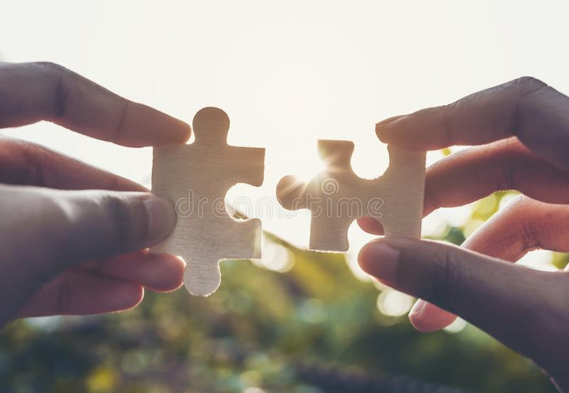 Businessmen hold jigsaw puzzles for each other. Business teamwork concept stock images