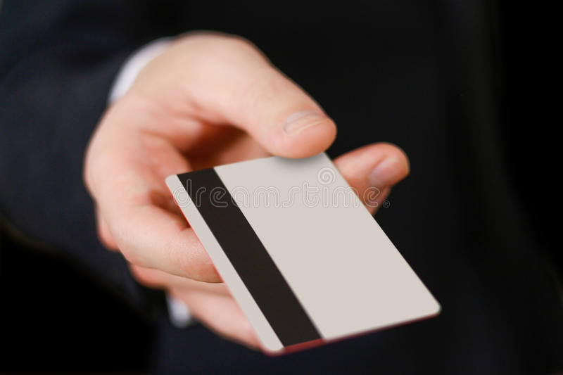Businessmen holding credit card proposing it to you. Hand in black suit holds out a blank grey credit card. Close up.  stock photos
