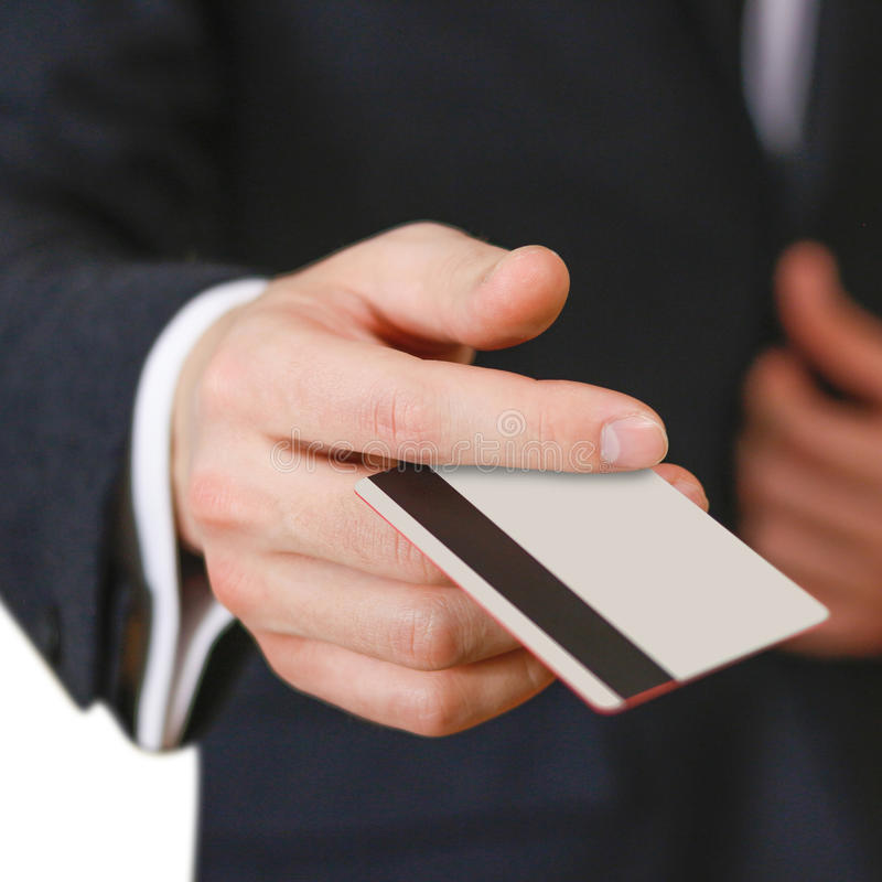 Businessmen holding credit card proposing it to you. Hand in black suit holds out a blank grey credit card. Close up. Businessmen holding credit card proposing royalty free stock photography