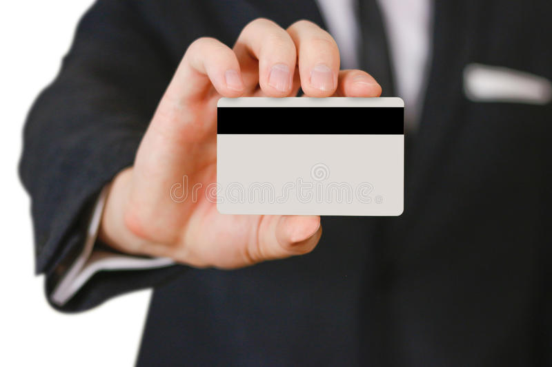 Businessmen holding credit card proposing it to you. Hand in black suit holds out a blank grey credit card. Close up. royalty free stock photography
