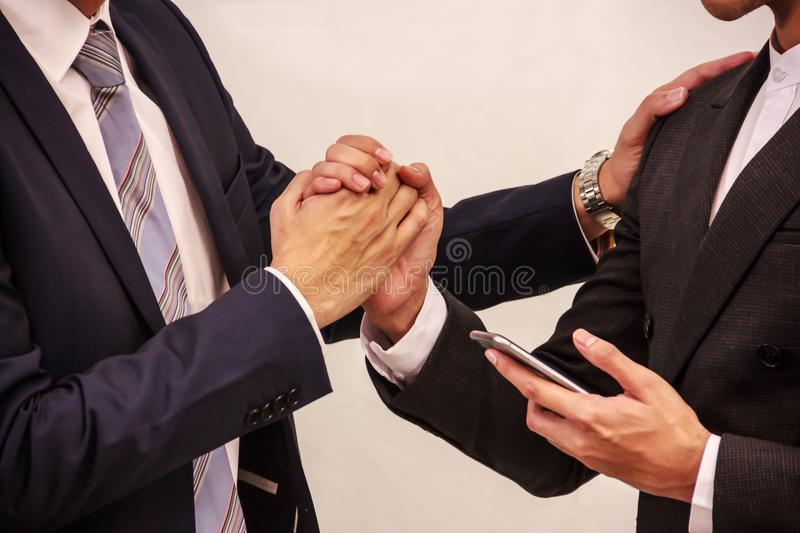 Businessmen holding hand after deal confirmed on the smart phone. Conceptual Idea of success, sale closed, transaction transfer stock photo