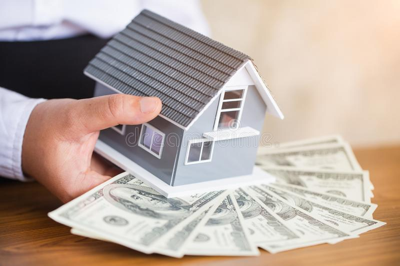 Businessmen holding money and red house models. Real estate loan concept stock photos