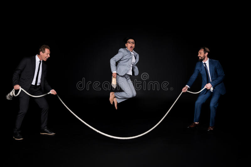 Businessmen holding rope while mature barefoot asian businesswoman jumping royalty free stock image