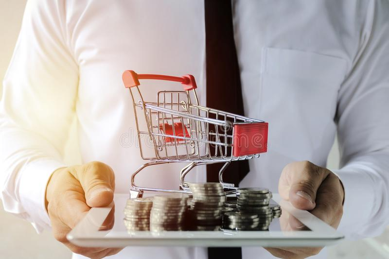 Businessmen are holding a tabloid with lots of coins and trolley. Business online concept. Businessmen are holding a tabloid with lots of coins and trolley. Easy stock images