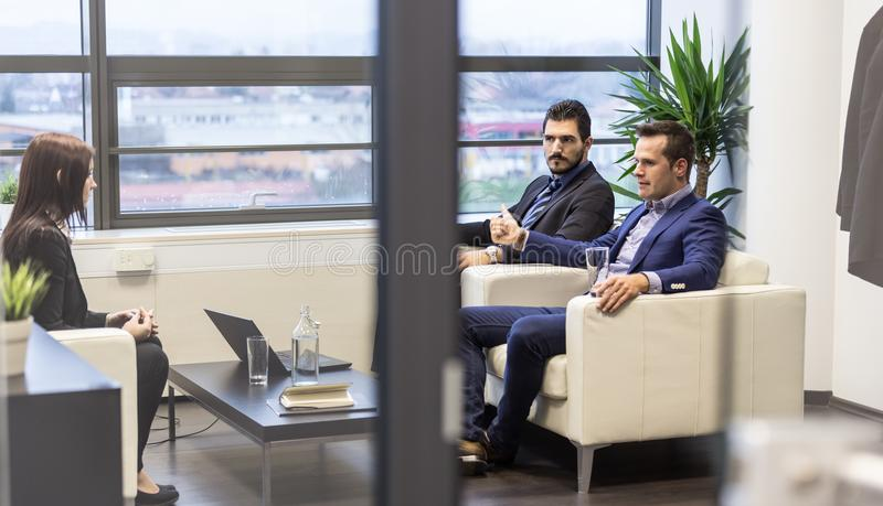 Businessmen interviewing female candidate for job in modern corporate office. stock image