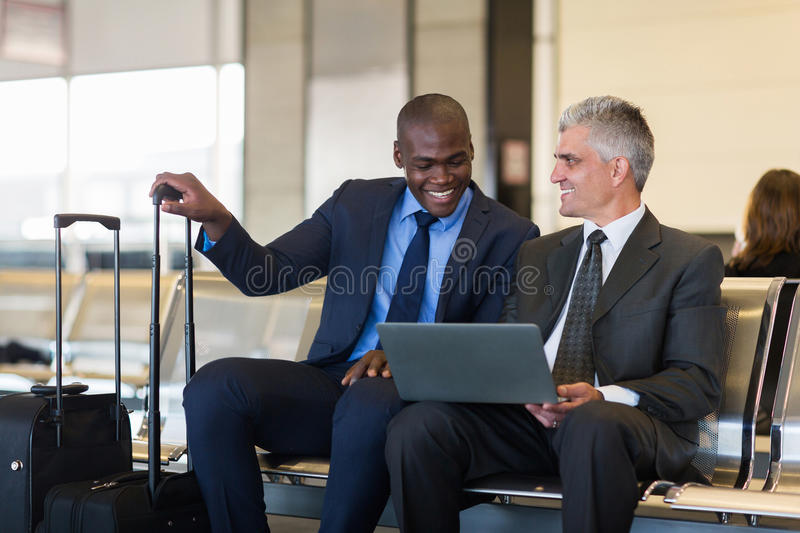 Businessmen laptop airport. Cheerful businessmen using laptop computer at airport stock images