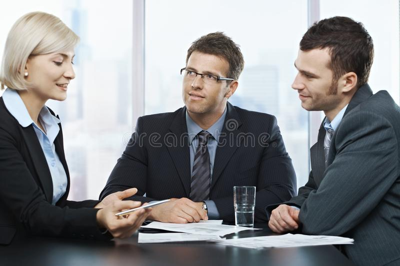 Businessmen listening to businesswoman. Explaining work at office meeting stock images
