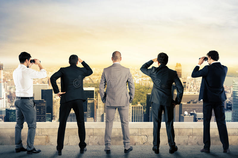 Businessmen looking to the future. Businessmen looks at the city from the roof with binoculars royalty free stock image