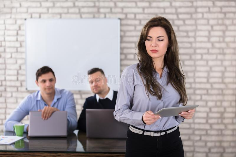 Businessmen Looking At Woman Holding Digital Tablet. Young Businesswoman Holding Digital Tablet In Front Of Two Businessman In Office royalty free stock photography