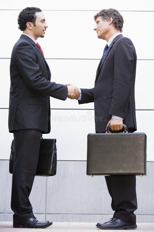 Businessmen meeting outside office stock image