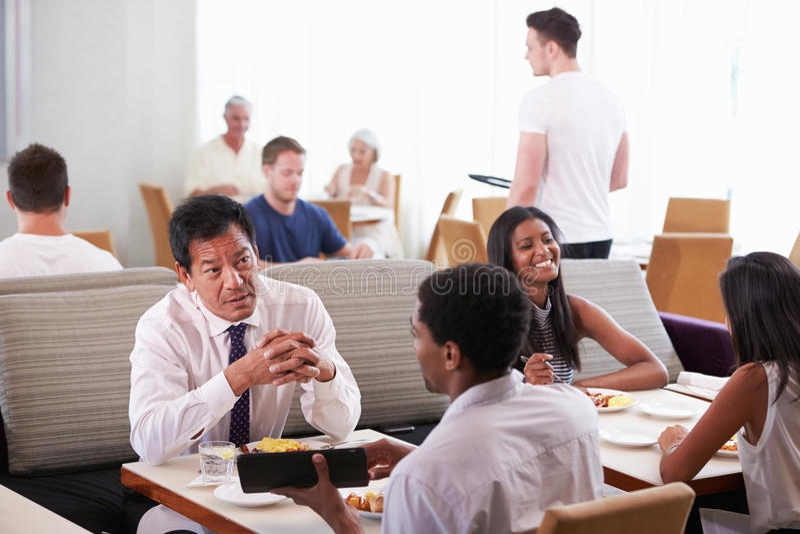 Businessmen Meeting Over Breakfast In Hotel Restaurant stock image