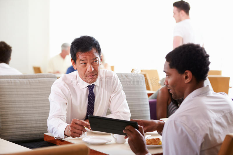 Businessmen Meeting Over Breakfast In Hotel Restaurant stock photography