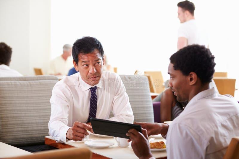 Businessmen Meeting Over Breakfast In Hotel Restaurant royalty free stock photos