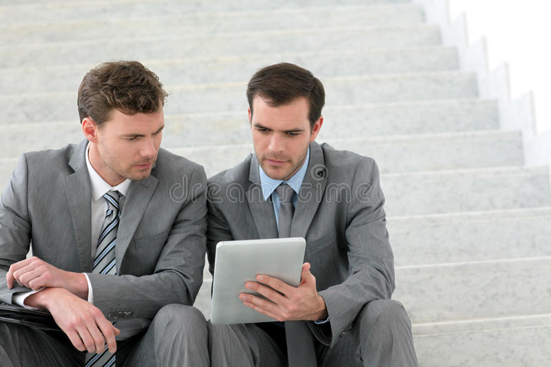 Businessmen meeting on stairs using tablet royalty free stock image