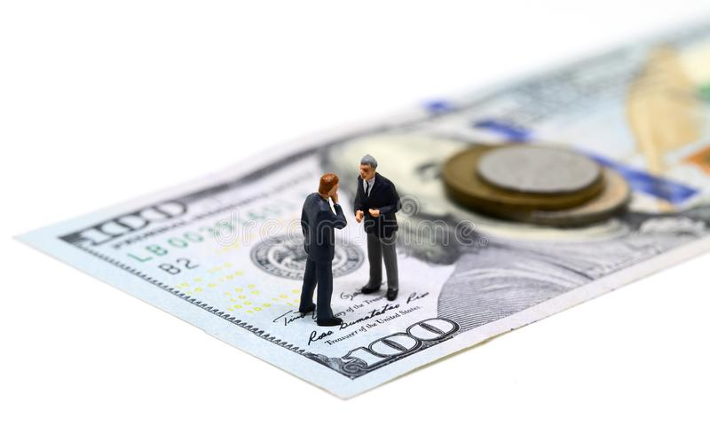 Businessmen miniature figurine macro photo. Cash money - USA banknote and coin. royalty free stock image