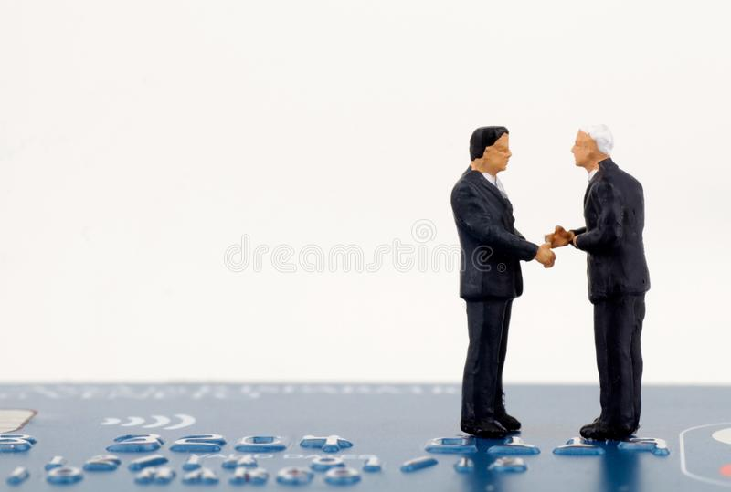 Businessmen miniatures agreeing. Over a credit card stock images