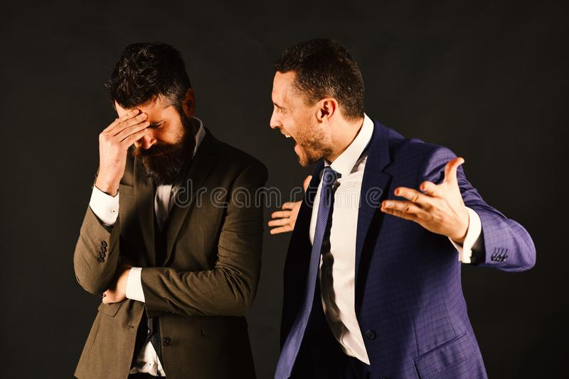 Businessmen quarreling loudly on black background. Business opposition concept. stock photos