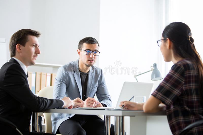 Businessmen recruit a young employee. At the office stock photo