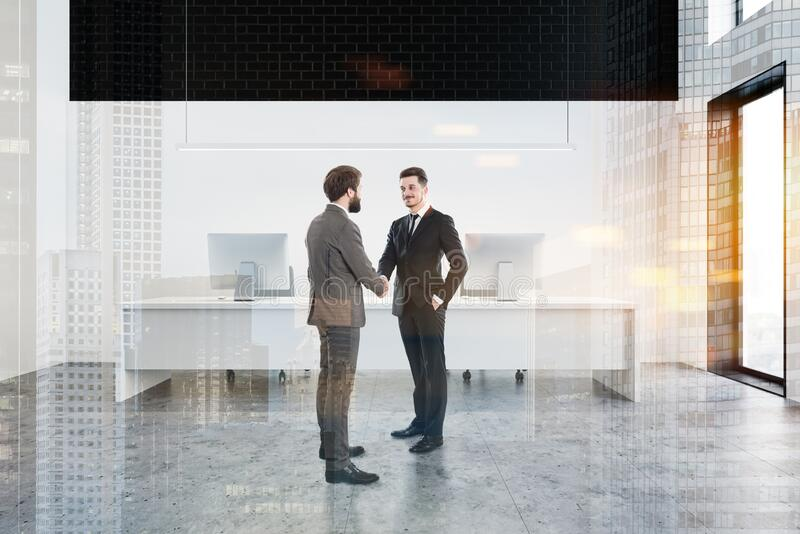 Businessmen shake hands in white and black office royalty free stock photography