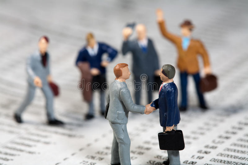 Businessmen shaking hands cheered on by the team stock image