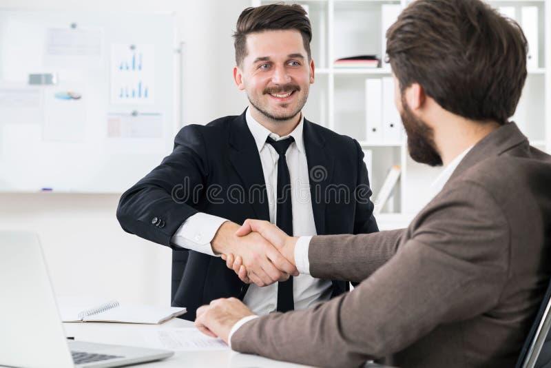 Businessmen shaking hands stock photos