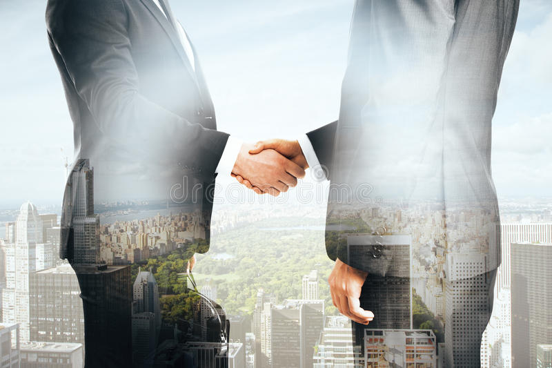 Businessmen shaking hands. On city background. Double exposure stock image