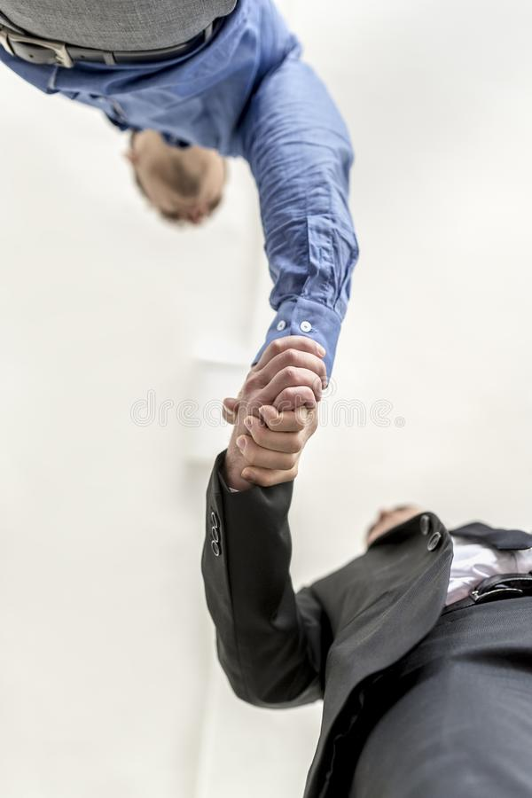 Businessmen shaking hands. On a deal or agreement , in welcome or in congratulations, low angle view stock photos