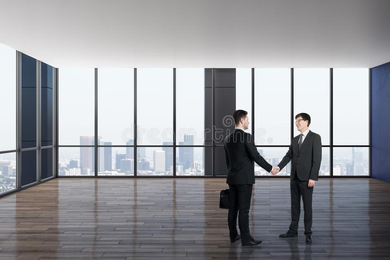 Businessmen shaking hands in luxury office interior stock photo