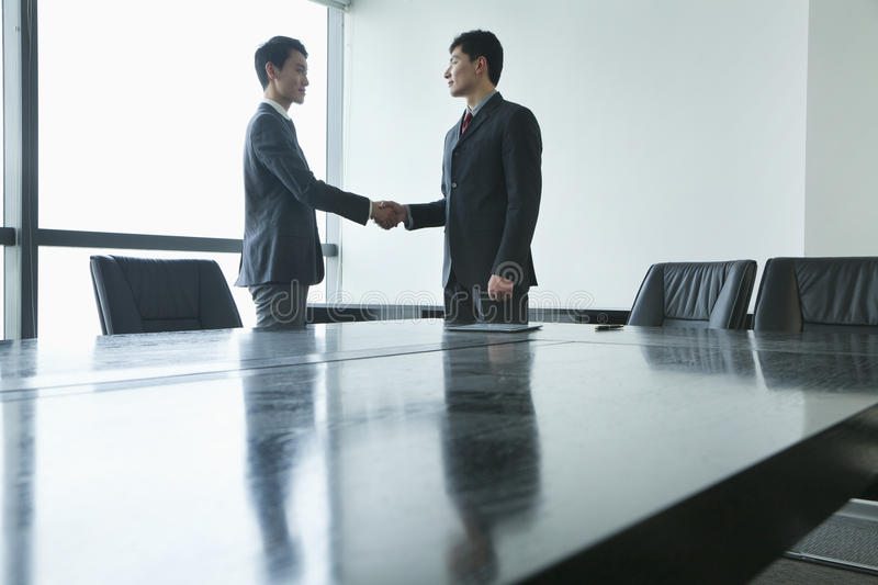 Businessmen shaking hands in meeting room royalty free stock image