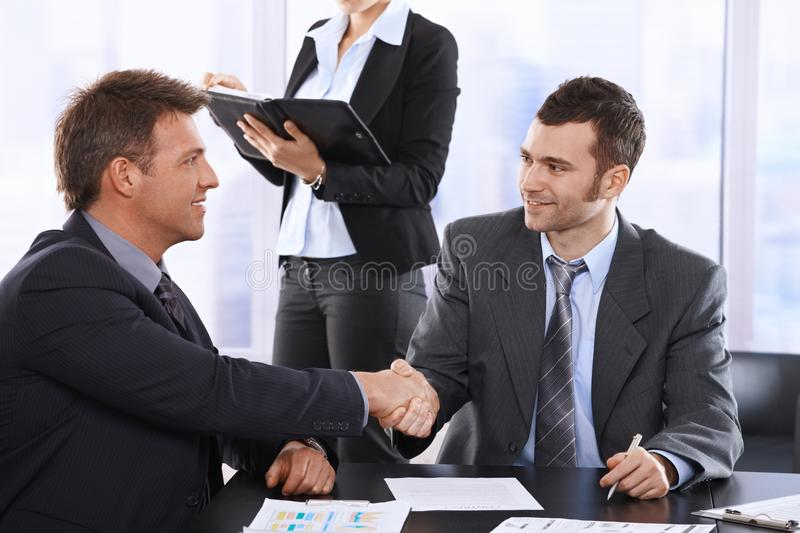 Businessmen shaking hands. At meeting, sitting at table, assistant in background holding organiser royalty free stock photography