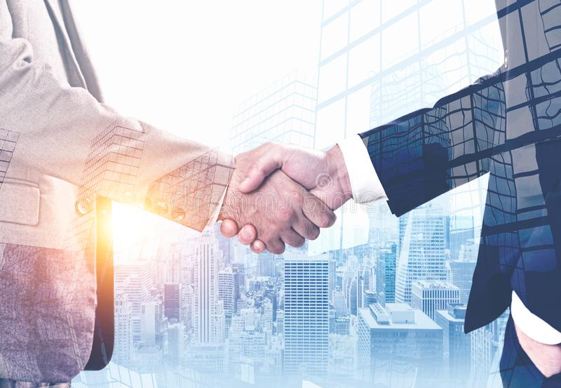 Businessmen shaking hands in morning city stock images