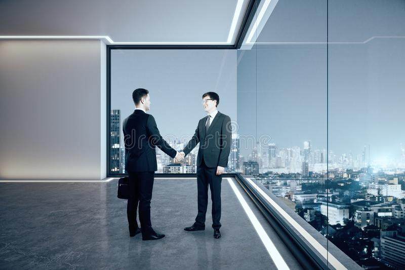 Businessmen shaking hands in office. Businessmen shaking hands looking out of window in modern empty spacious office interior with illuminated panoramic city stock images