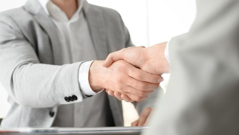 Businessmen shaking hands in office. Closeup stock images