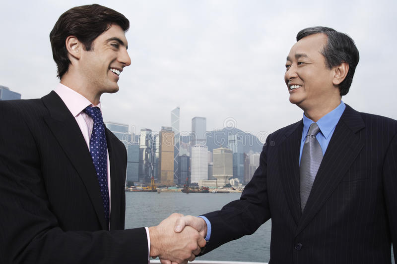Businessmen Shaking Hands Outdoors stock images