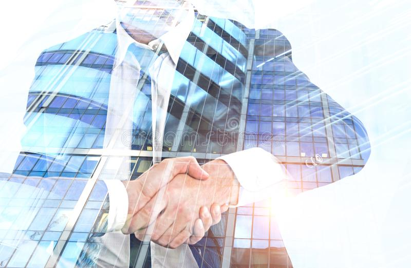 Businessmen shaking hands, skyscrapers royalty free stock photos