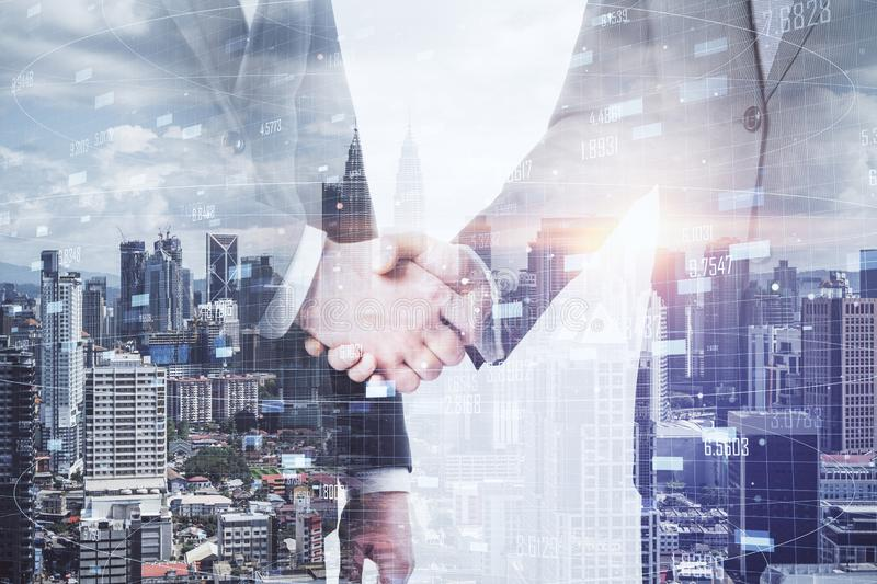 Businessmen shaking hands. Sode view of businessmen shaking hands on blurry Kuala Lumpur city background. Partnership and success concept. Multiexposure royalty free stock photography
